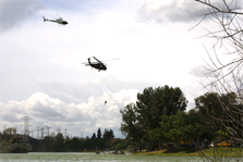 A civilian helicopter transporting a film crew circles above an Army Blackhawk helicopter as it executes a simulated rooftop evacuation on the set of the Army National Guard's new recruiting commercial.  The National Guard worked with the Los Angeles District to secure a filming permit for the shoot, which took place at Whittier Narrows Park March 8.